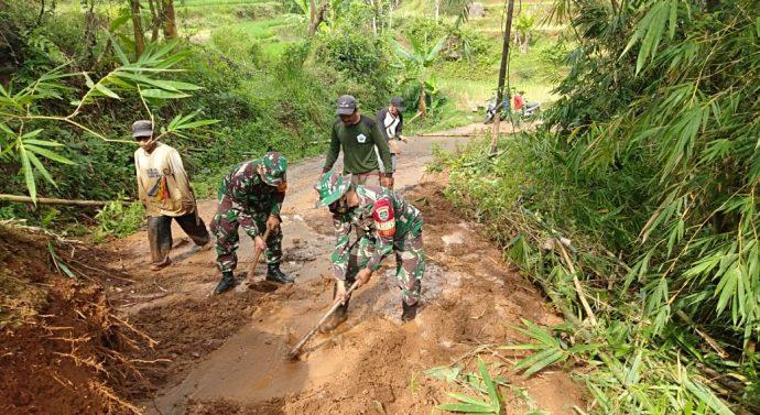 Babinsa Koramil 1107/Limbangan bersama warga membersihkan jalan akibat longsor