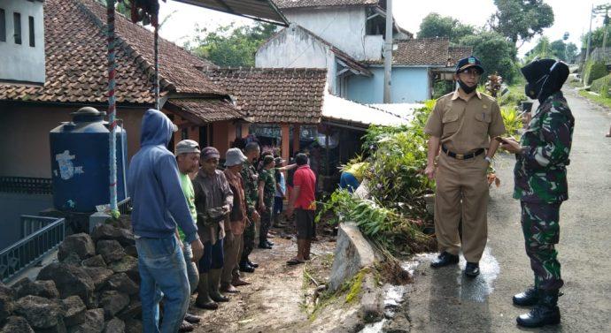 Kapten Caj (K) Muji Rahayu Danramil 1102/Karangpawitan meninjau rumah terkena longsor di Sindanggalih